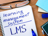 Notepad with learning management system LMS   on office wooden table.